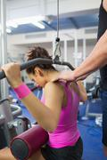 Stock Photo of Trainer correcting shoulder position of woman of working out