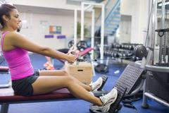 Stock Photo of Sporty brunette training arms on weight machine
