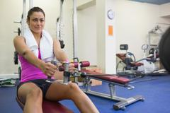 Urheilullinen nainen koulutusta aseiden paino kone Kuvituskuvat