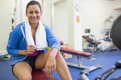 Smiling sporty brunette sitting on bench Stock Photos