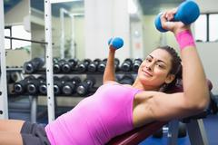 Happy brunette lying on bench working out with dumbbells - stock photo