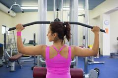 Toned woman exercising on weight machine - stock photo