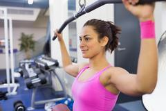 Stock Photo of Content woman exercising on weight machine