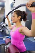 Calm woman exercising on weight machine - stock photo