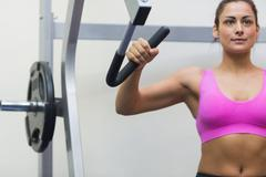 Stock Photo of Calm sporty brunette training her arms