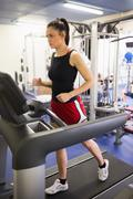 Determined sporty brunette running on treadmill Stock Photos