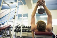 Stock Photo of Muscular man holding heavy dumbbell over head