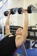 Muscular happy man lying on bench training with dumbbells - stock photo