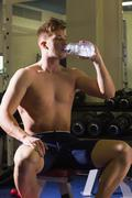 Stock Photo of Muscular man sitting on bench drinking from water bottle