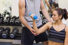 Stock Photo of Instructor correcting serious woman lifting dumbbells