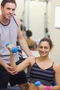 Instructor correcting happy woman lifting dumbbells Stock Photos