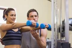 Stock Photo of Instructor assisting happy woman lifting dumbbells