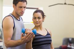 Instructor assisting sporty brunette lifting dumbbells - stock photo
