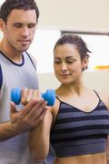 Instructor assisting content brunette lifting dumbbells - stock photo