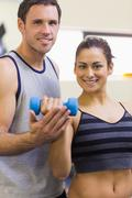 Instructor assisting smiling brunette lifting dumbbells - stock photo