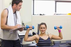 Stock Photo of Instructor taking notes of smiling brunette lifting dumbbells