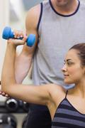 Stock Photo of Trainer correcting calm woman lifting dumbbells