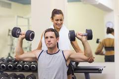 Trainer correcting muscular man lifting dumbbells - stock photo