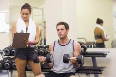 Stock Photo of Trainer taking notes of attractive man lifting dumbbells