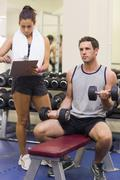 Stock Photo of Trainer taking notes of muscular man lifting dumbbells