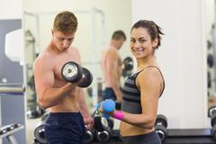 Determined man and smiling woman holding dumbbells - stock photo