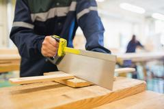 Carpenter sawing wood - stock photo