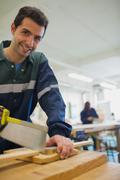 Smiling carpenter sawing wood - stock photo