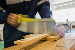 Craftsman sawing piece of wood - stock photo