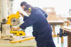Concentrating trainee sawing piece of wood Stock Photos