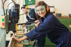 Smiling trainee with safety glasses drilling wood - stock photo