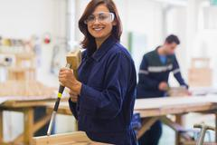 Smiling trainee using mallet and chisel - stock photo