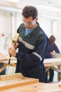 Carpenter using mallet and chisel - stock photo