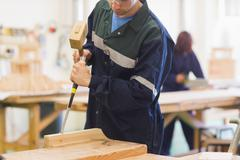 Craftsman using mallet and chisel - stock photo