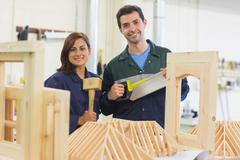 Cheerful trainee and instructor standing behind construction - stock photo