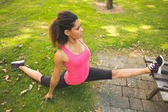 Flexible young woman doing the splits exercise in park Stock Photos