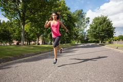 Full length of a healthy woman jogging on pathway in park - stock photo