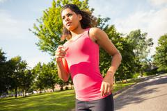 Beautiful healthy woman jogging on pathway in park - stock photo