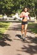 Beautiful healthy young woman jogging on pathway in park - stock photo