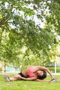 Toned and flexible woman doing stretching exercise in park Stock Photos