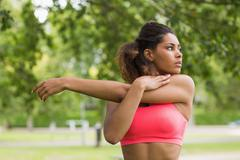 Serious healthy young woman stretching her hand at park - stock photo