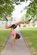 Toned woman performing a handstand in park - stock photo