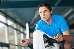 Determined young man working out at spinning class - stock photo