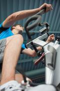 Determined man working out at spinning class in gym - stock photo