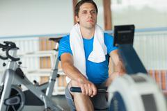 Determined young man working out on row machine - stock photo