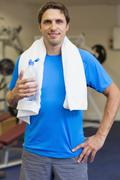 Portrait of a smiling man with water bottle in gym - stock photo