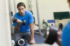 Determined man with dumbbell in fitness studio - stock photo
