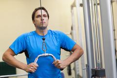 Man doing exercises in the gym on lat machine Stock Photos