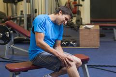 Healthy man with an injured leg sitting in gym - stock photo