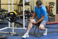 Healthy man with an injured leg sitting in the gym Stock Photos