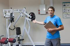 Stock Photo of Trainer with clipboard pointing toward lat machine in gym